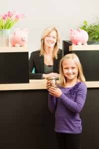 Girl depositing jar of savings at bank
