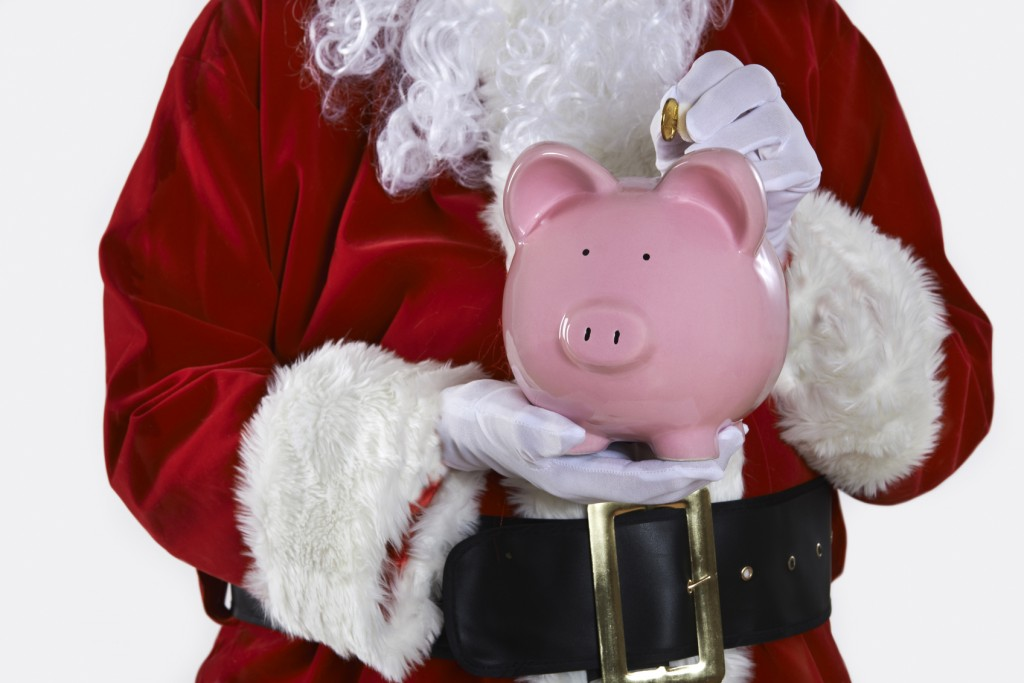Close Up Of Santa Claus Putting Coin Into Piggy Bank