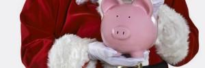 Close Up Of Santa Claus Putting Coin Into Piggy Bank